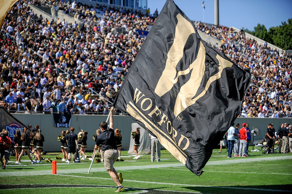 Student running Wofford flag across the football field