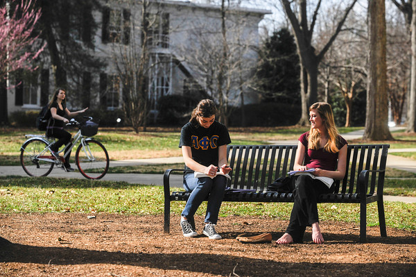 2 students sitting on bench together outside
